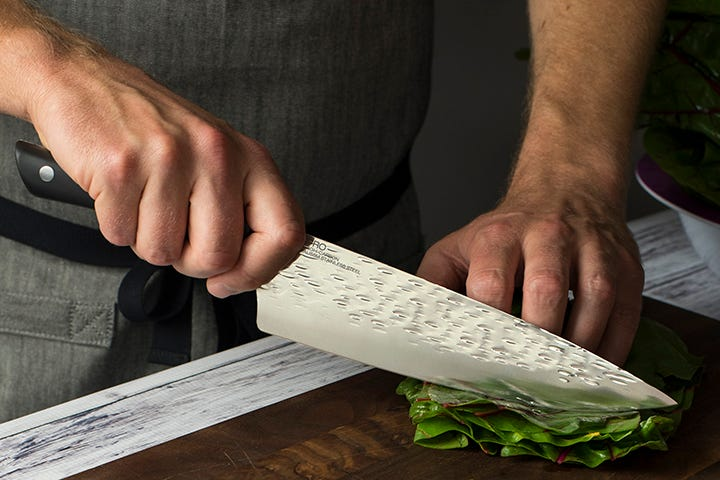 Chef's knife correctly slicing chard